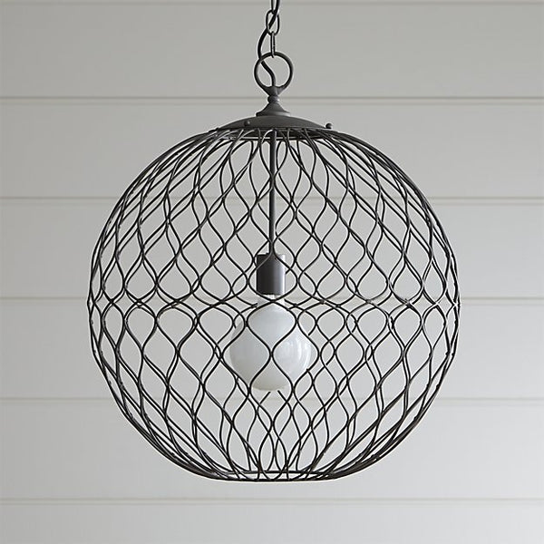 A pretty woven iron globular pendant lamp shot in front of a shiplap panel.