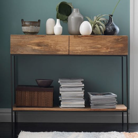 An industrial console table with 2 storage drawers, a shelf underneath, and iron legs.