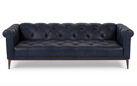 A tufted chesterfield sofa with navy denim leather upholstery and wooden legs