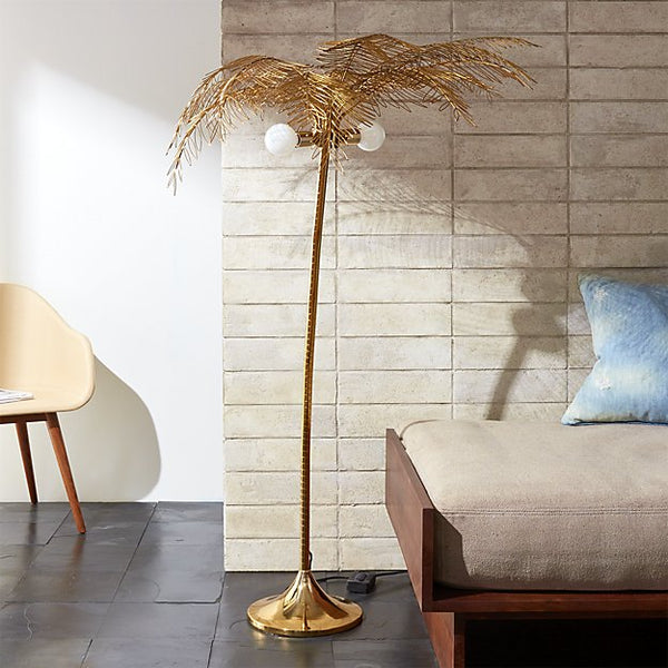 A tall gold floor lamp shaped like a palm tree with two bulbs pictured against a faux exposed-brick wall.