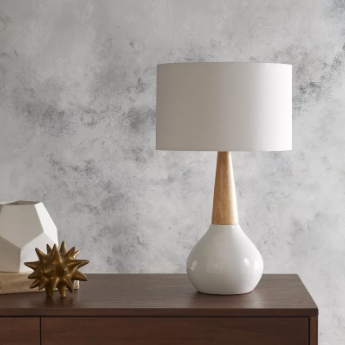 A white porcelain lamp with a bulbous bottom, a neck made of solid wood, and a white linen shade.
