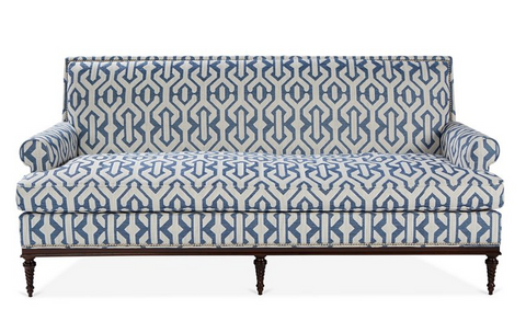 A 3 seater sofa with traditional lines and blue and white geometric upholstery and wooden legs. On a white background.