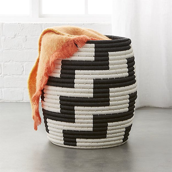 A handwoven graphic black and white basket with an orange throw draped over the side.