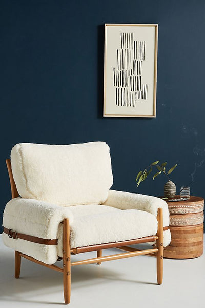 A white wool chair in a blue room. Chair features removable wool cushions, leather belting, and looks as if it is from the 1950s. Scandinavian look.