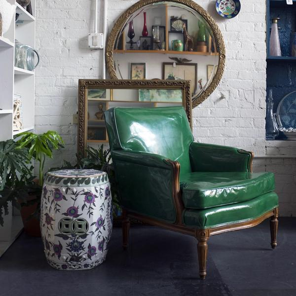 A vintage green patent leather chair with a ceramic floral garden stool.
