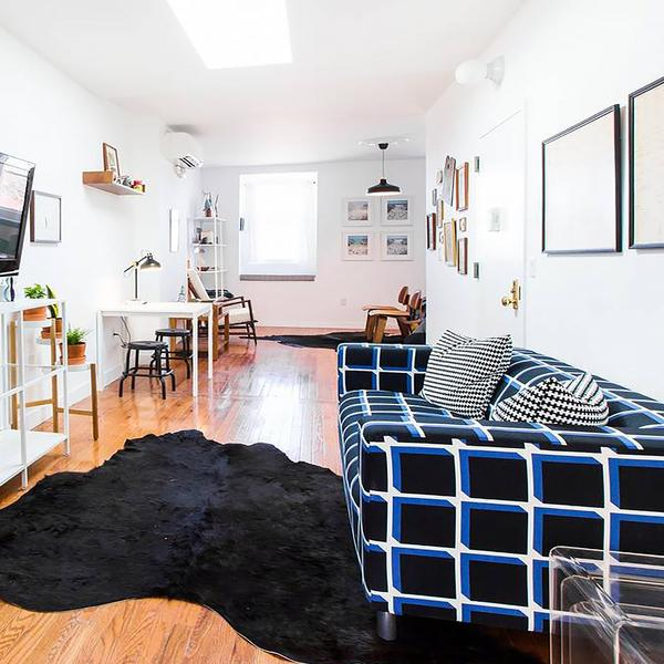 An apartment with a black plaid sofa, black cowhide rug, white kitchen table and white shelving.