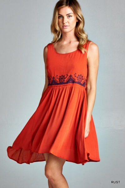 Babydoll dress featuring delicate embroidery around waistline. Rust