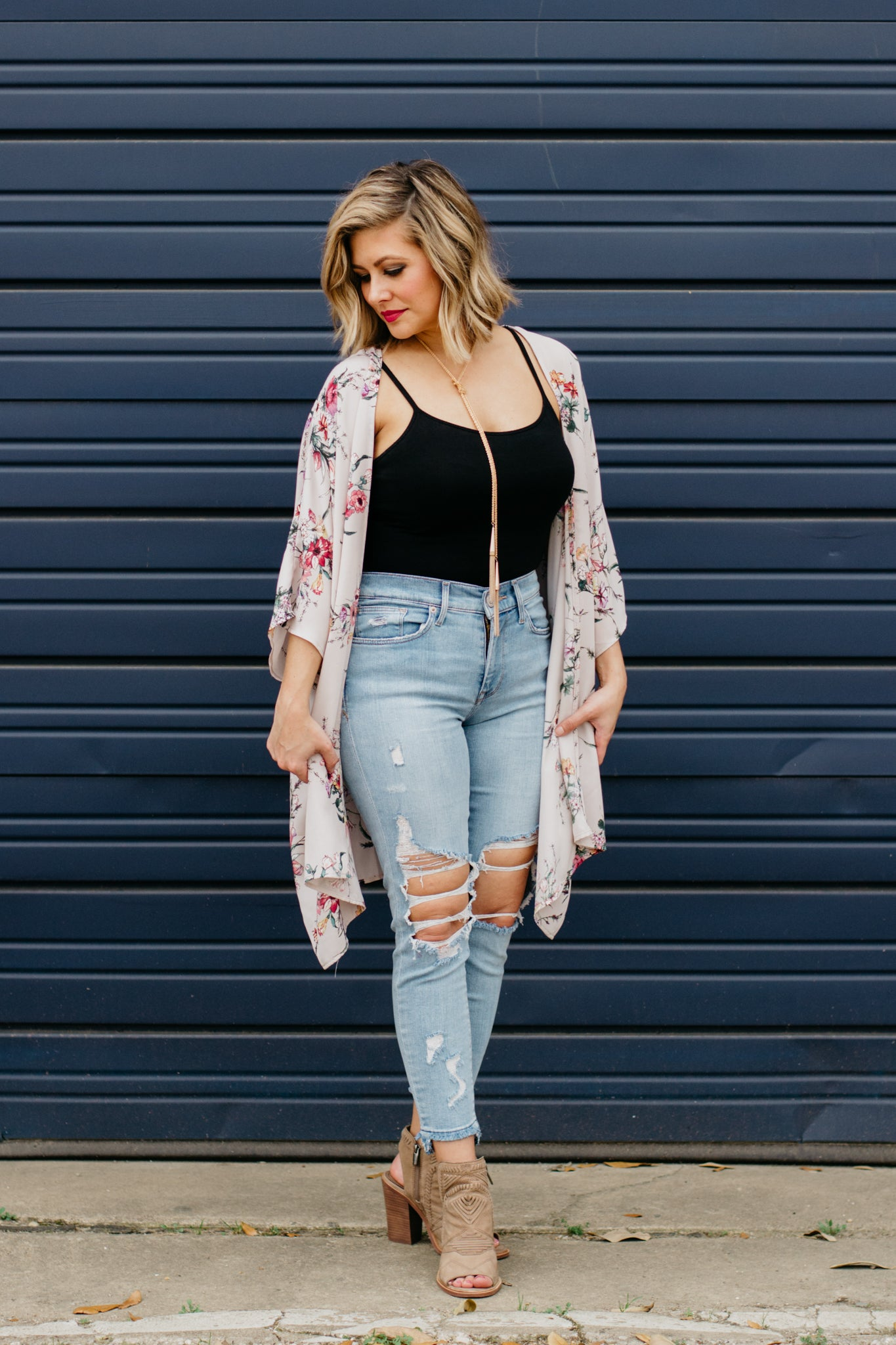 Distressed denim and booties paired with mauve floral kimono