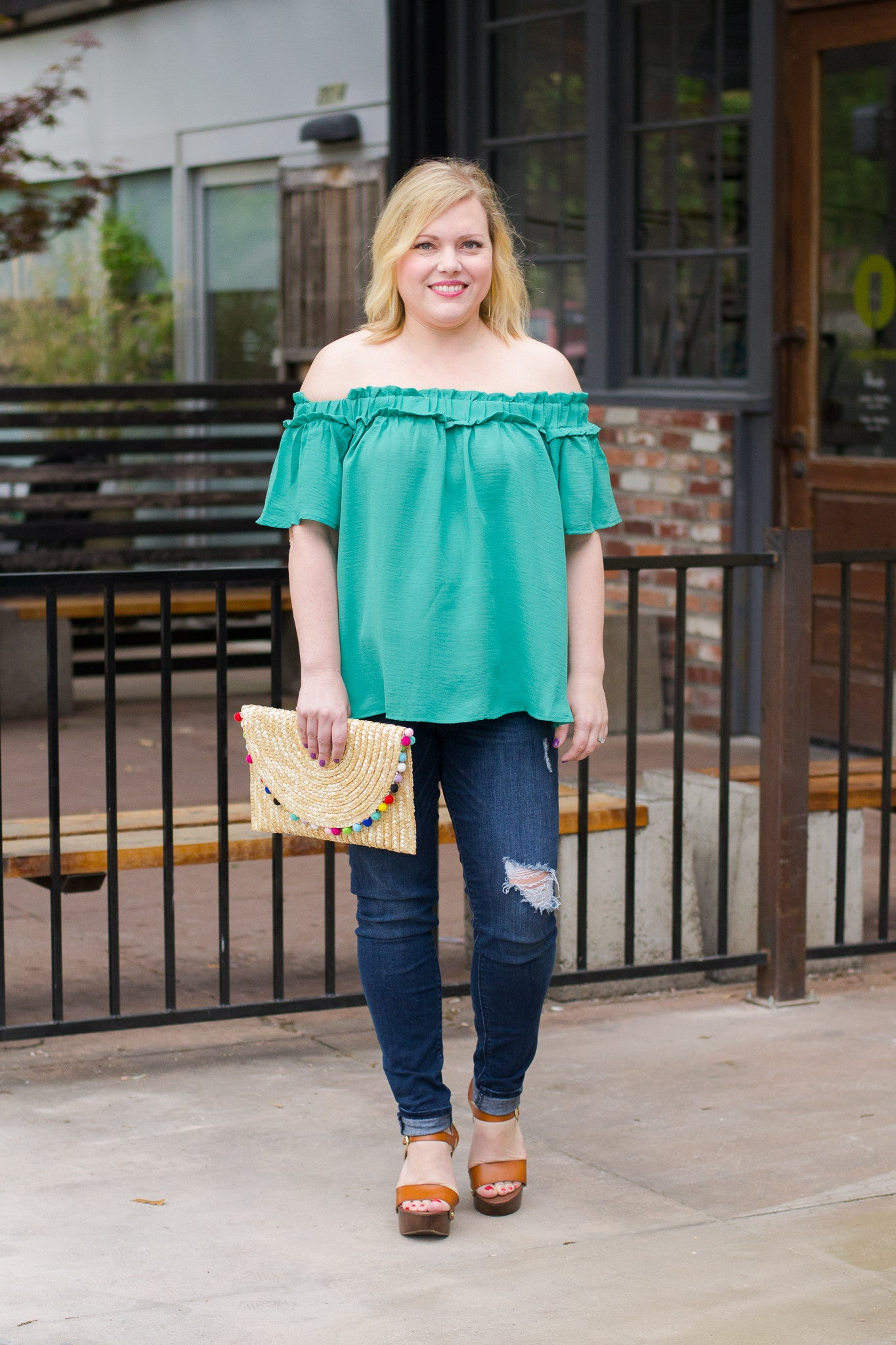 Off the shoulder top paired with pom pom clutch