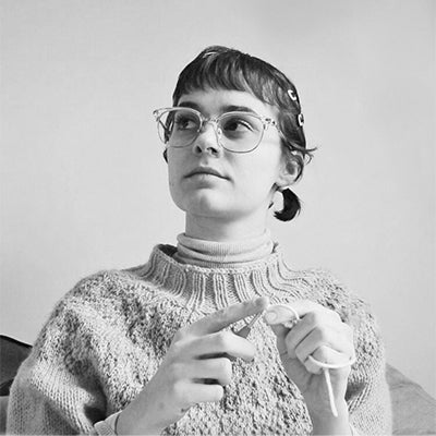 Photo of a person crocheting and looking upwards