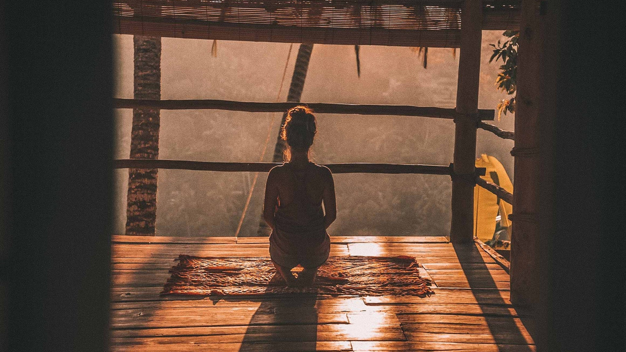 girl meditating on a deck during sunrise