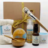TruSelf Organics Lucky You Holiday Gift Box with gold ribbon, and products Detox Mask, Clear Skin Foaming Cleanser, Skin Drenching Face Serum, Ocean Mineral Moisturizer, Bamboo Utensil Set & Bamboo Cloth