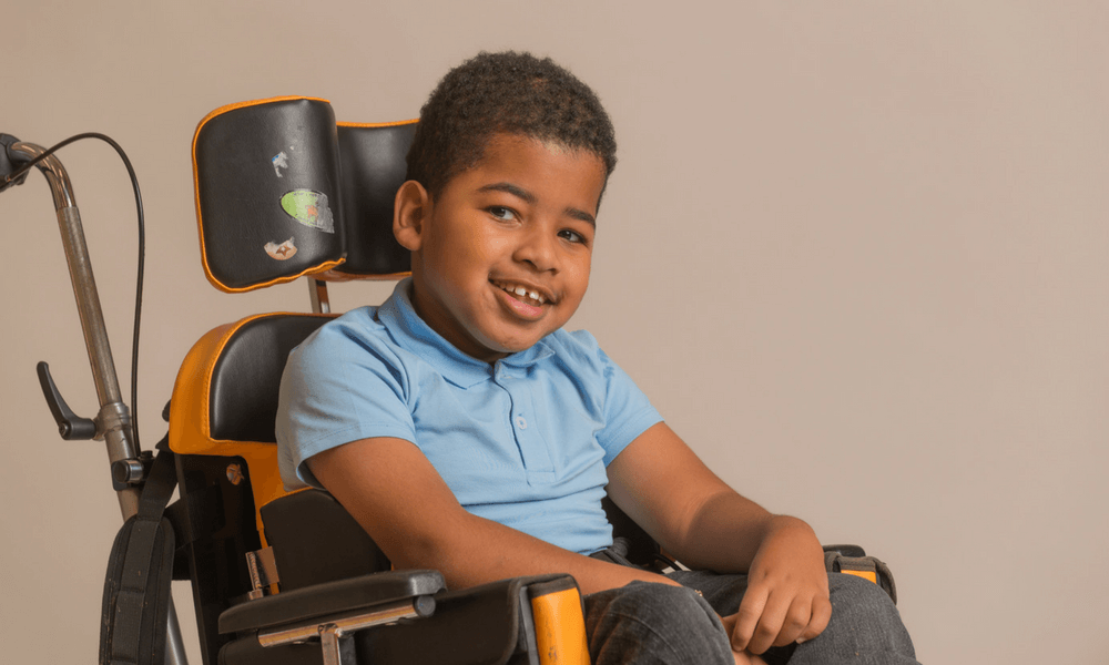 Boy wearing KayCey Supersoft blue polo bodysuit for older children with special needs