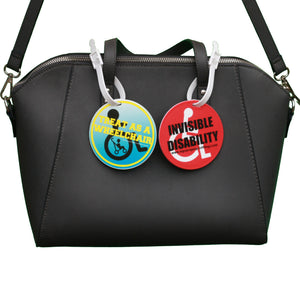 square_peg_invisible_disability_and_treat_as_wheelchair_user_badge_clips_on_bag