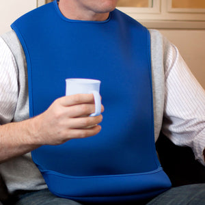 CareDesign_large_tabard_for_special_needs_adult_wearing_a_blue_bib_with_feeding_pouch