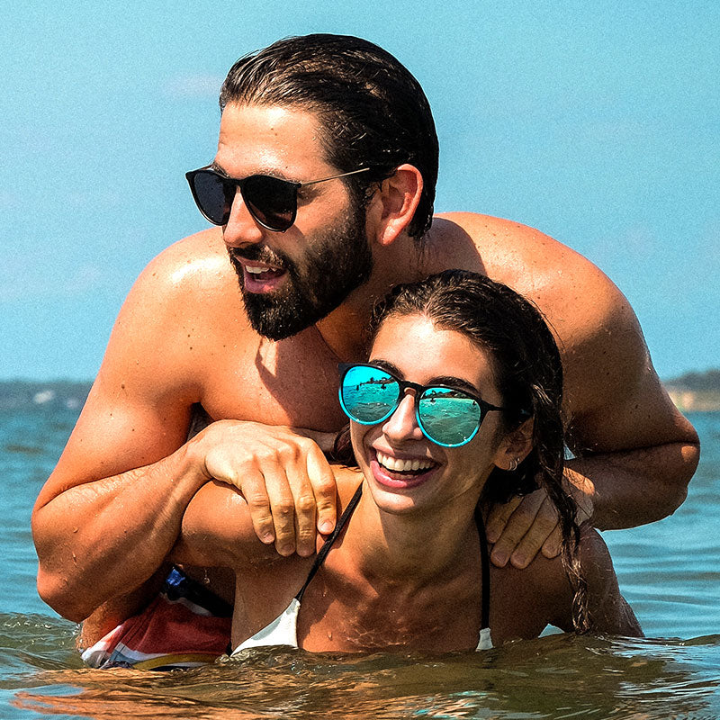 Photo showing young couple in the ocean wearing polarized Gage sunglasses