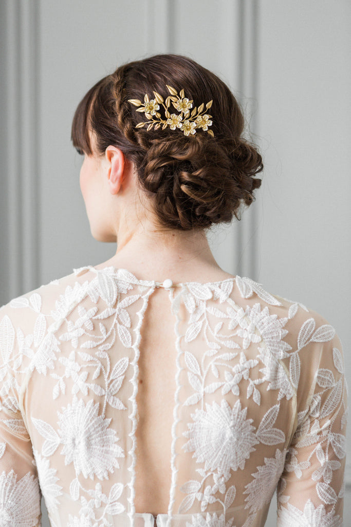 A model wearing a bridal hair comb made of gold leaves