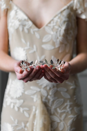 Bride holding a delicate silver leaf tiara