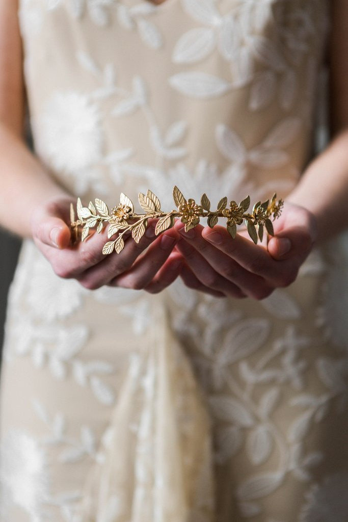 Bride holding a gold leaf bridal tiara