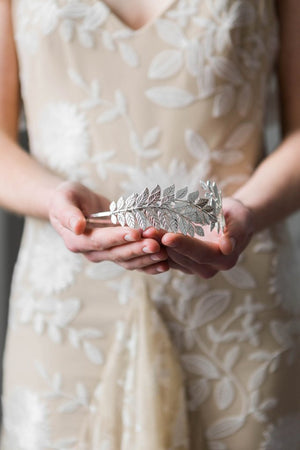 Bride holding a silver leaf headpiece