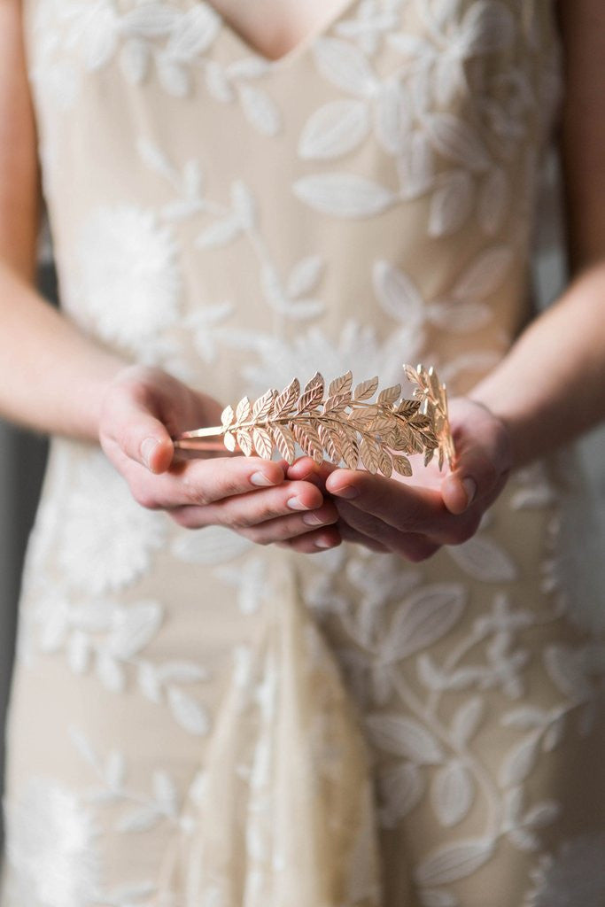 Model holding a bridal headpiece made of gold leaves
