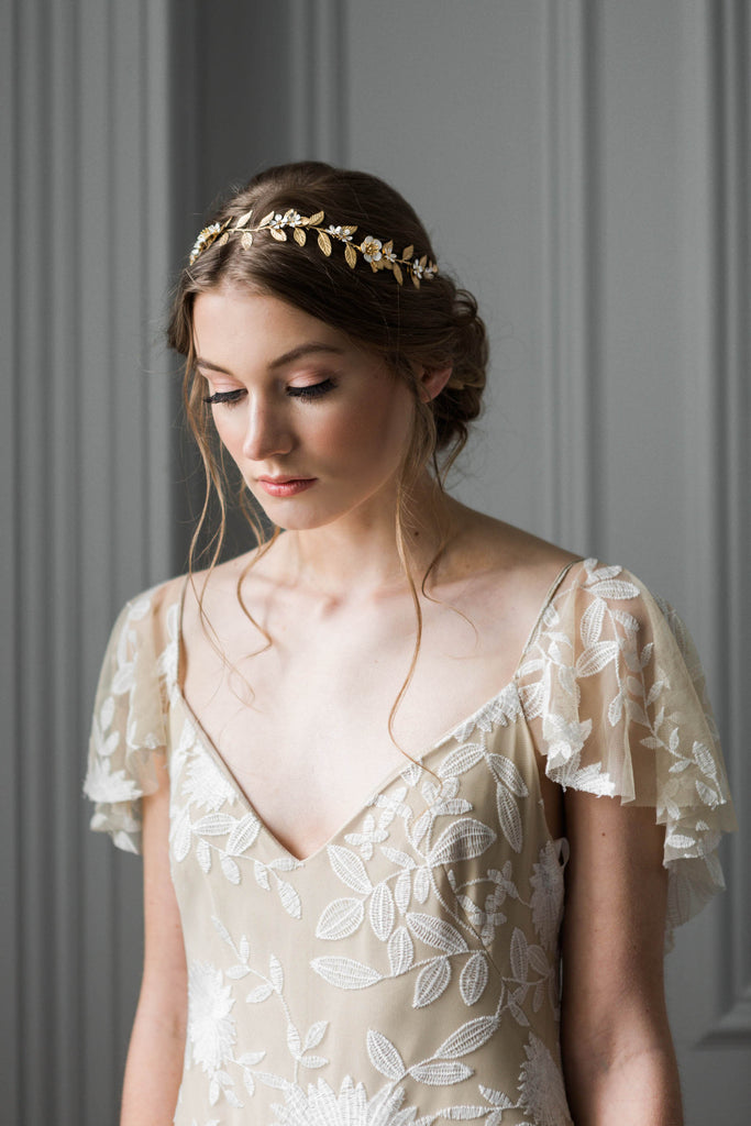 Bride holding a headpiece made of gold vines and flowers