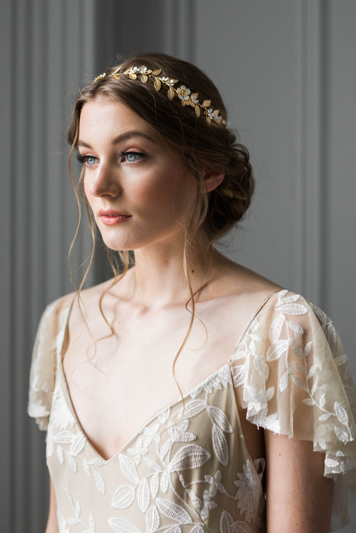 Bride in wedding dress wearing a headpiece made of gold vines