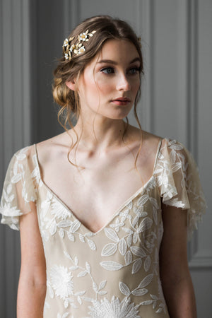 Model wearing a bridal wrap headpiece made of gold vines