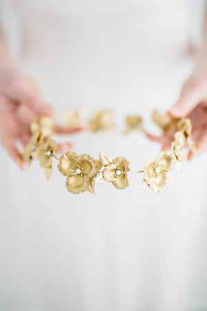 Bride holding a circlet crown made of gold flowers