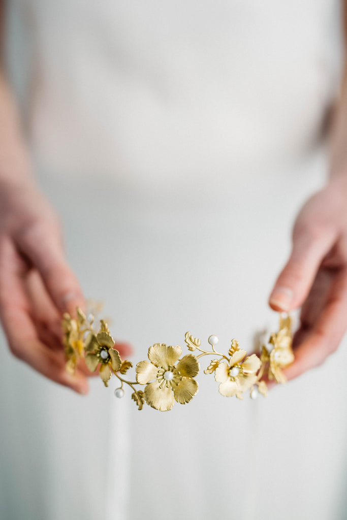 Bride holding a headpiece made of gold flowers and leaves