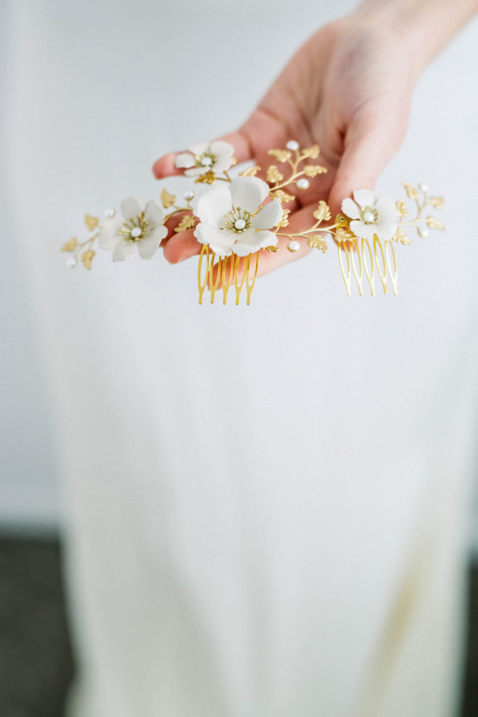 Bride holding a headpiece made of gold leaves and ivory flowers