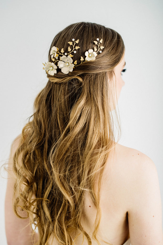 Bride wearing a headpiece made of gold leaves and ivory flowers