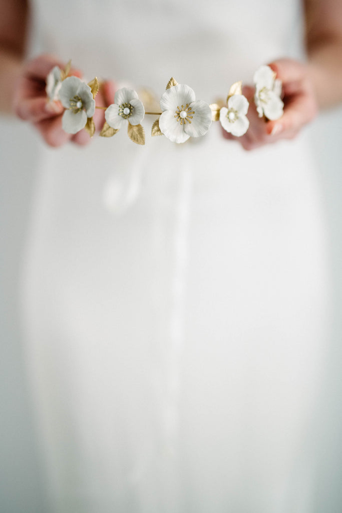 Bride holding a circlet crown made of gold and ivory flowers
