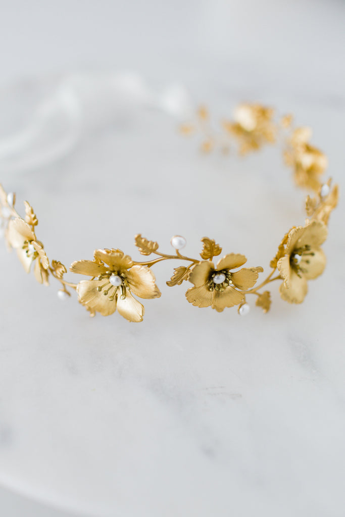 Close up a headpiece made of gold flowers and leaves