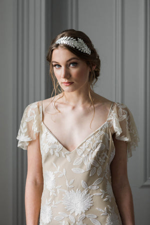 Model wearing a bridal headpiece made of silver leaves