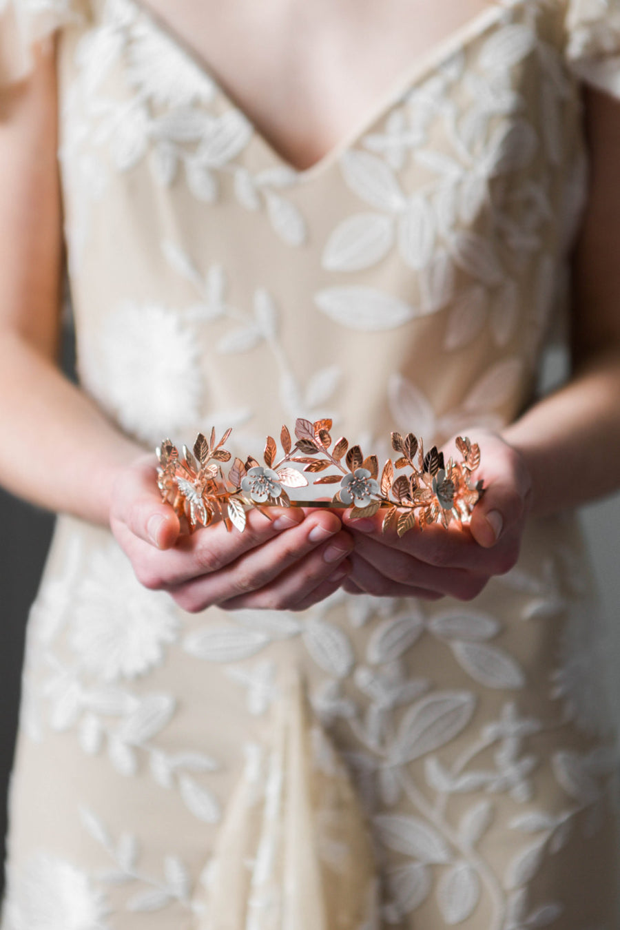 A bride wearing a rose gold laurel leaf flower crown
