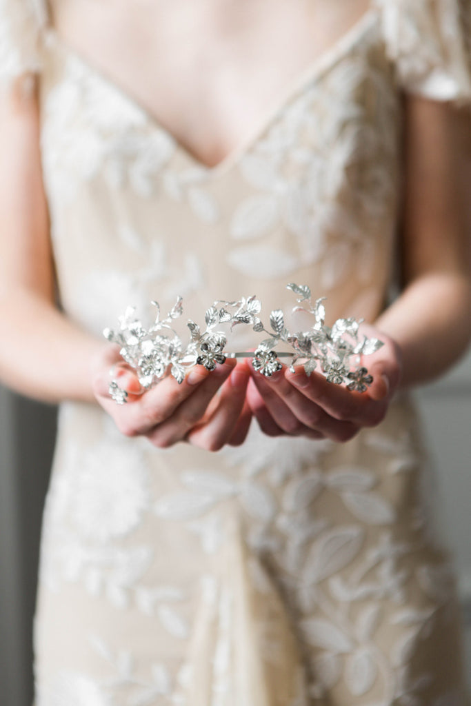 Bride holding a silver headpice made replica antique myrtle leaves