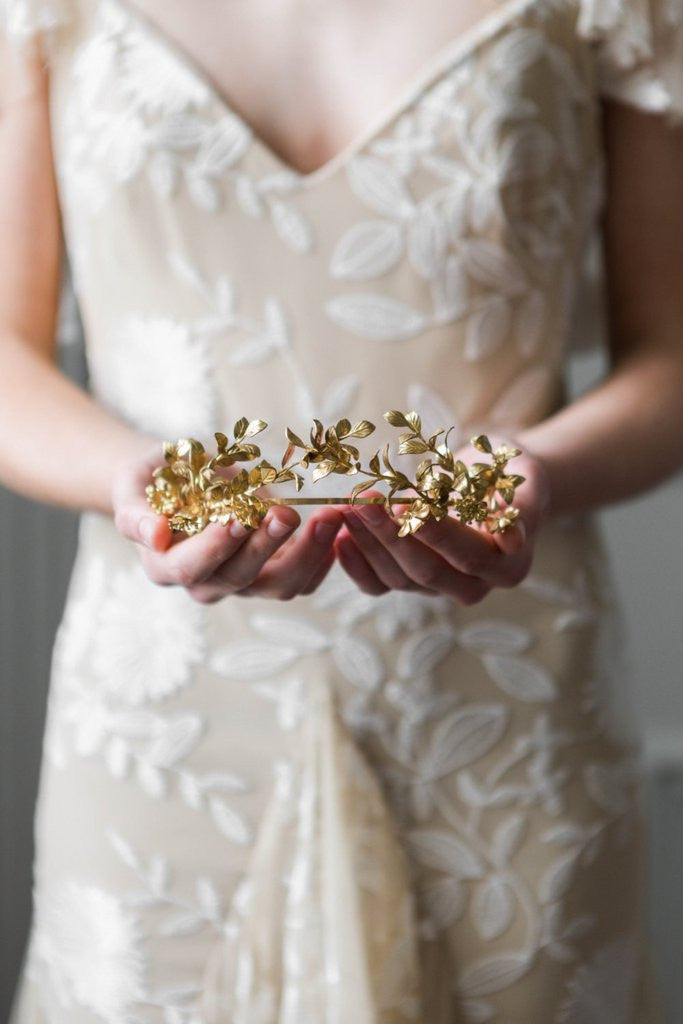 Bride holding a gold headpice made replica antique myrtle leaves
