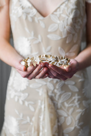 Bride holding a crown heapiece made of gold leaves and silk flowers