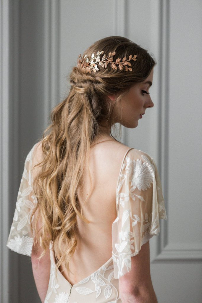 Model in wedding dress wearing a gold bridal headpiece