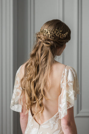 Model wearing a gold laurel leaf bridal headpiece on the back of her head