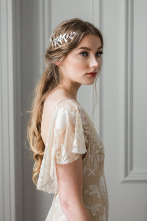 Model in white gown wearing a silver laurel leaf bridal heapiece wrapped around back of head