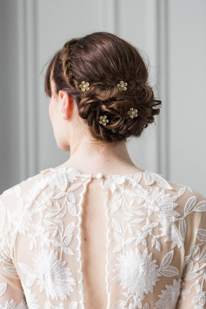 Model with hair pins in her bun wearing a wedding dress
