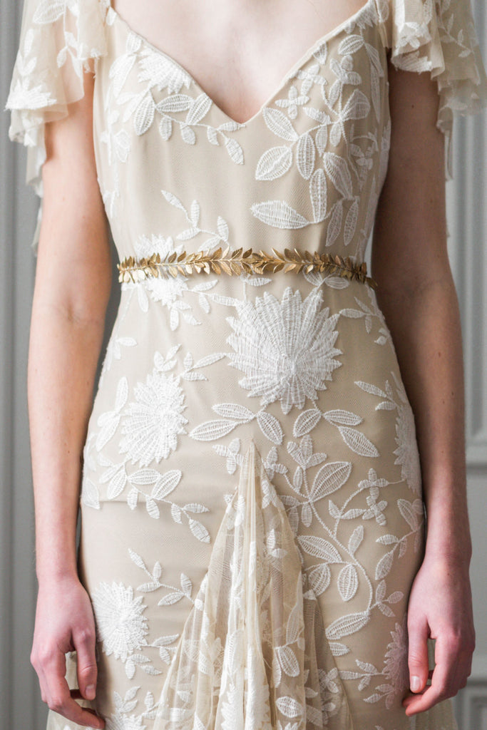 Bride in a wedding dress wearing a gold leaf sash