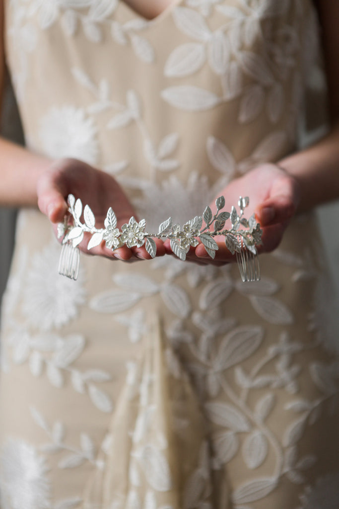 Bride holding a headpiece made of silver leaves
