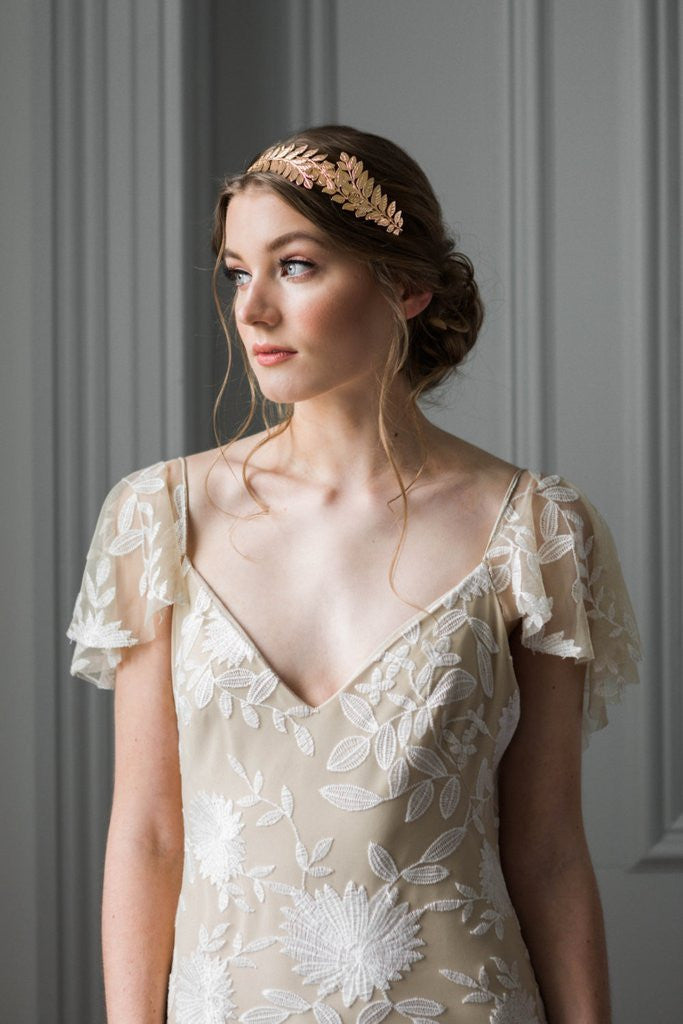 Model wearing a bridal headpiece made of gold leaves