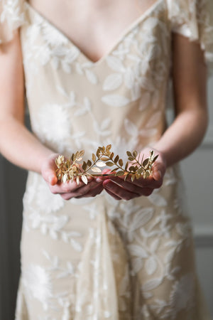 Bride holding a gold laurel leaf tiara