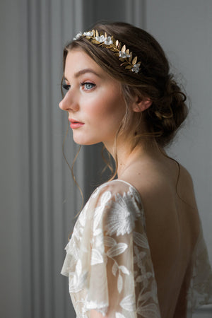 Bride wearing a crown heapiece made of gold leaves and silk flowers