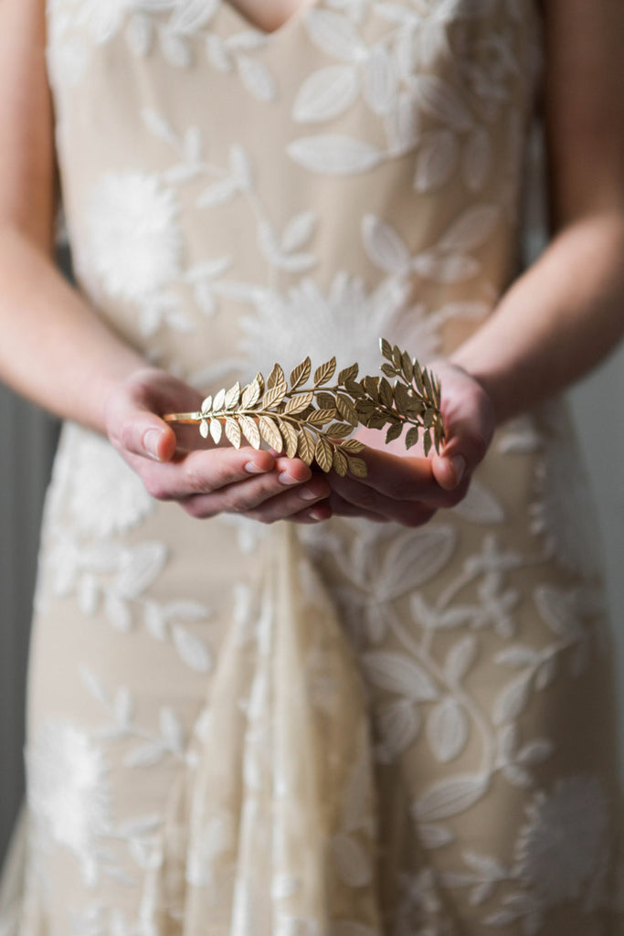 Bride holding a gold leaf headpiece