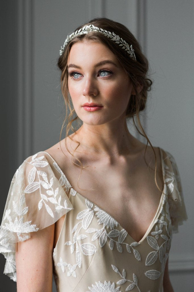 Model in a wedding dress wearing a silver Edwardian leaf bridal tiara